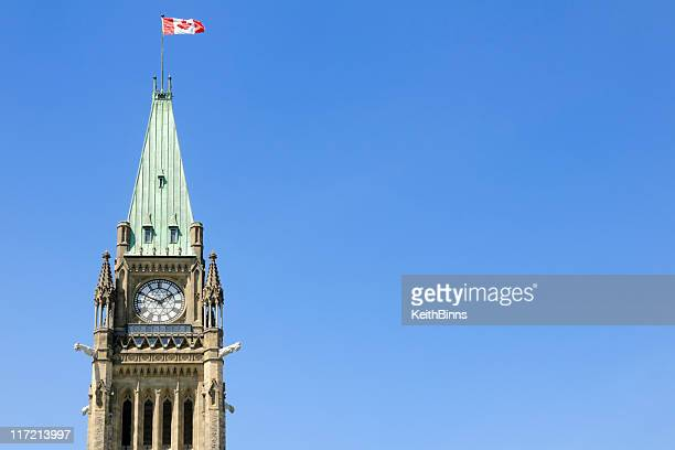 the peace tower with a canadian flag waving in the air - tower stock pictures, royalty-free photos & images