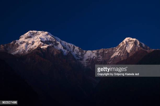 The peak of Annapurna South and Hinchuli during the evening twilight time in Chhomrong.