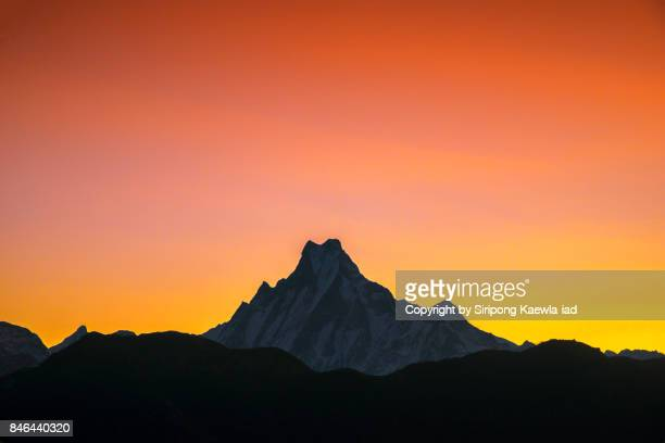The peak of Machapuchchre mountain with red-orange sky during sunrise from Poon Hill viewpoint.