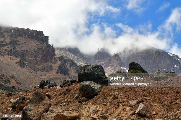 the peaks and crags of kibo in the clouds - rotswand stockfoto's en -beelden