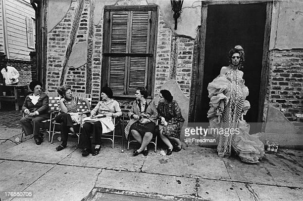 The pearl queen poses next to group of women deep in conversation New Orleans 1973