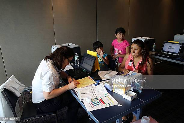 The Pedraza family fills out paperwork at the Yankees / Lincoln Hospital BacktoSchool Immunization Fair on September 1 2015 in New York City The...