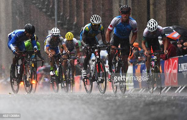 The peloton makes its way along the streets of Glasgow in heavy rain in the Men's Road Race during day eleven of the Glasgow 2014 Commonwealth Games...