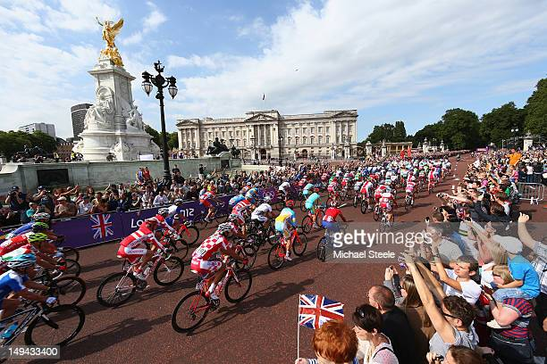 The peloton passes the Queen Victoria Memorial and Buckingham Palace during the start of the men's 249.5km road race on day one of the 2012 Olympics...