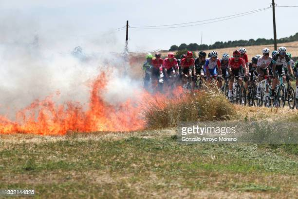 The Peloton passing close to a fire during the 43rd Vuelta a Burgos 2021, Stage 1 a 161km stage from Burgos-Catedral to Burgos-Alto del Castillo 980m...
