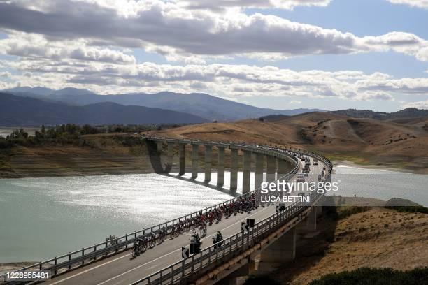 The peloton rides across a bridge over Lago di Monte Cotugno during the 6th stage of the Giro d'Italia 2020 cycling race, a 188-kilometer route...