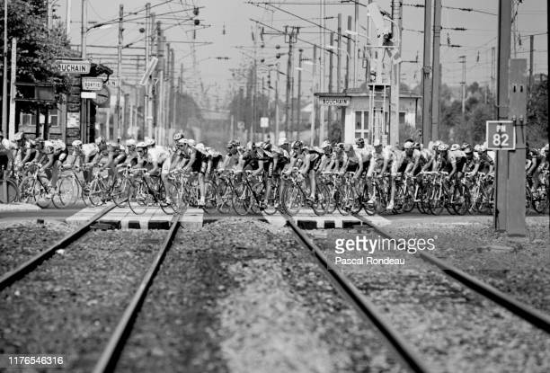 The peloton rides across the railway tracks at Bouchain on stage two of the Tour de France from Roubaix to Boulogne-sur-Mer on 4th July 1994 near...
