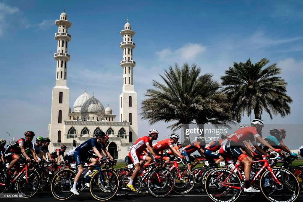 The peloton rides past a mosque near Sultan Qaboos University during the second stage of the 2018 cycling Tour of Oman, from Sultan Qaboos University to Al-Bustan, west of the capital Muscat on February 14, 2018. / AFP PHOTO / Philippe LOPEZ