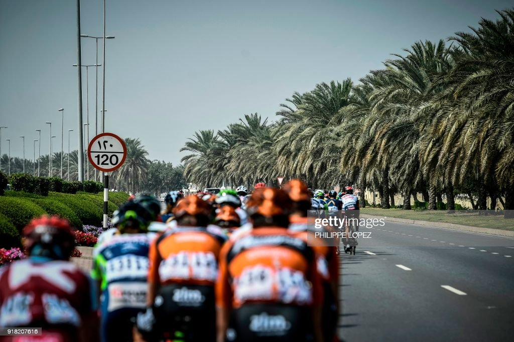 The peloton rides past palm trees near Al-Manumah during the second stage of the 2018 cycling Tour of Oman, from Sultan Qaboos University to Al-Bustan, west of the capital Muscat on February 14, 2018. / AFP PHOTO / Philippe LOPEZ