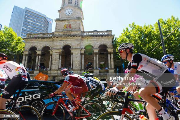 The peloton rides past the Adelaide Town Hall on the second day of the Tour Down Under cycling race in Adelaide on January 17 2018 / AFP PHOTO /...
