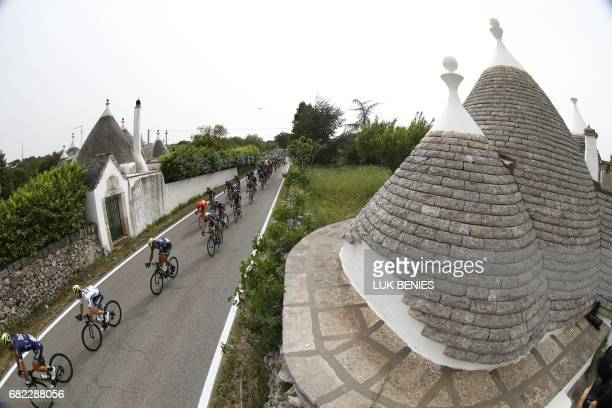 The peloton rides past traditionals 'trulli' of the Puglia region near Alberobello during the 7th stage of the 100th Giro d'Italia Tour of Italy...