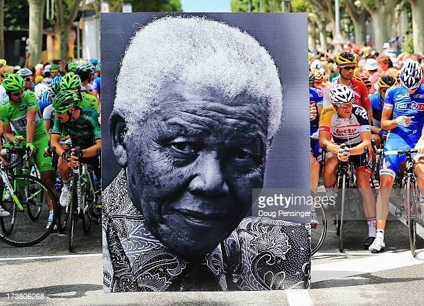 The peloton waits behind a large picture commemorating the birthday of former South African President Nelson Mandela before stage eighteen of the...