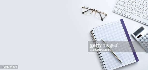 the pen is on an open notepad. next to the calculator, glasses and laptop. a blank sheet of notebook with the items of a businessman or accountant. concept of financial reporting. banner. - elektronische organiser stockfoto's en -beelden