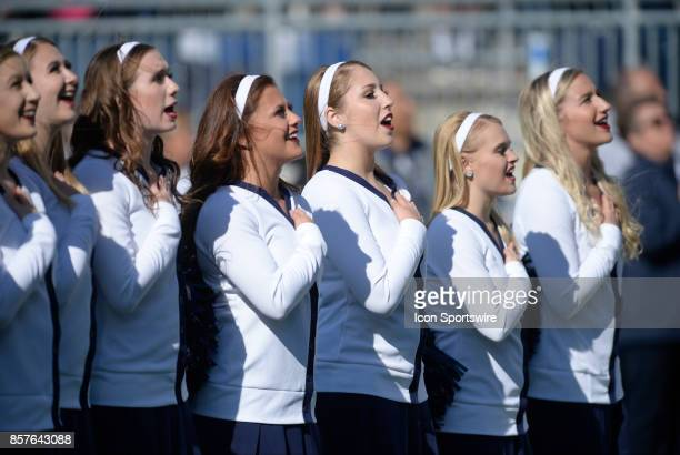 The Penn State Lionettes Dance Team wears throwback uniforms with white sweaters and hairbands with hands over hearts during the national anthem of...