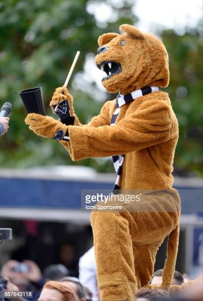 The Penn State Nittany Lion mascot plays hit a cow bell with a drum stick before the game during a college football game between the Indiana Hoosiers...