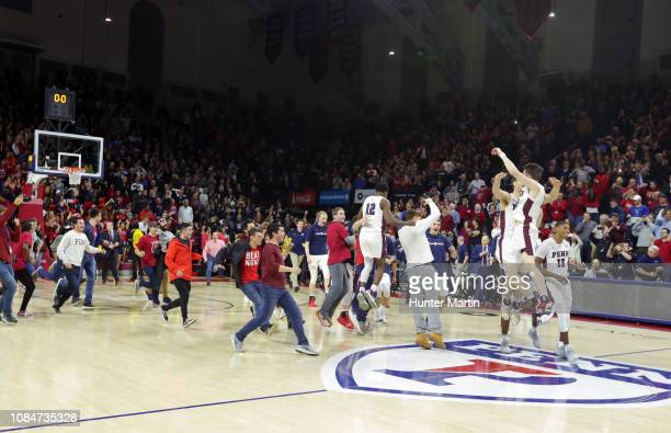 The Pennsylvania Quakers celebrate as fans storm the court after winning a game against the Villanova Wildcats at The Palestra on the campus of the...