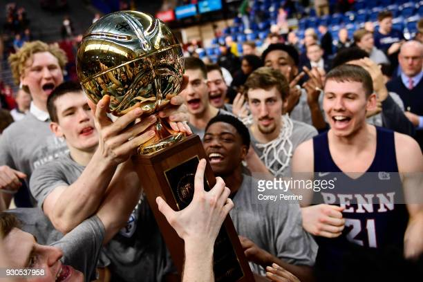 The Pennsylvania Quakers men's basketball team hold up the championship trophy after winning the Men's Ivy League Championship Tournament at The...