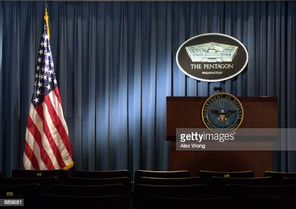 The Pentagon logo and an American flag are lit up January 3 2002 in the briefing room of Pentagon in Arlington VA