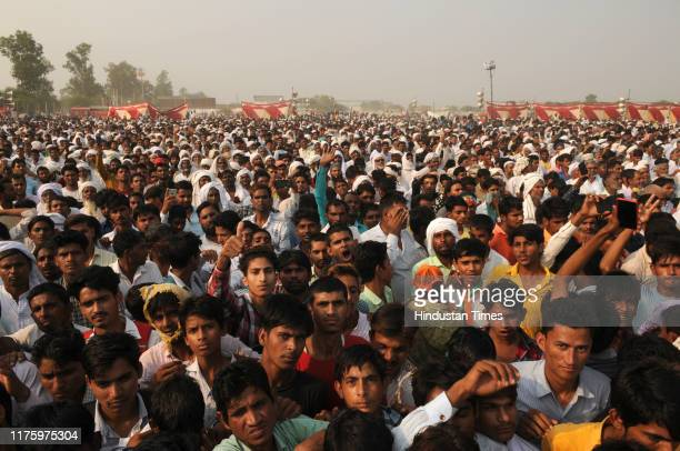 The people listen to a speech by Former Congress president Rahul Gandhi during the Parivartan rally at Maroda village near ITI on October 14 2019 in...
