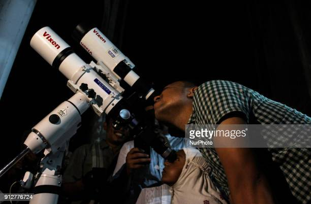 The people see the phenomenon of a lunar eclipse through a telescope in Lhokseumawe Aceh Province Indonesia on January 31 2018 This rare lunar...