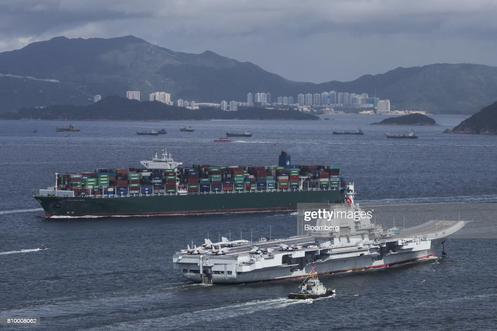 The People's Liberation Army (PLA) Liaoning aircraft carrier, bottom, sails past a container ship in Hong Kong, China, on Friday, July 7, 2017. The carrier will visit Hong Kong between July 7 and 11. Photographer: Justin Chin/Bloomberg via Getty Images