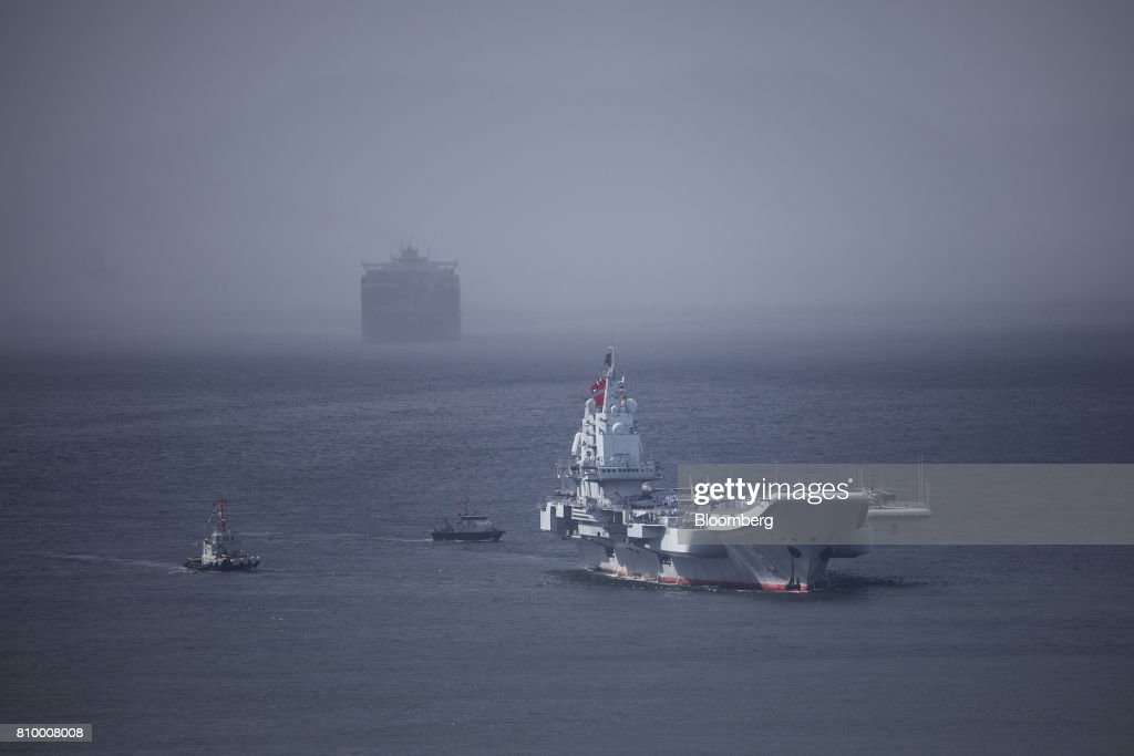 The People's Liberation Army (PLA) Liaoning aircraft carrier, front, sails into Hong Kong, China, on Friday, July 7, 2017. The carrier will visit Hong Kong between July 7 and 11. Photographer: Justin Chin/Bloomberg via Getty Images