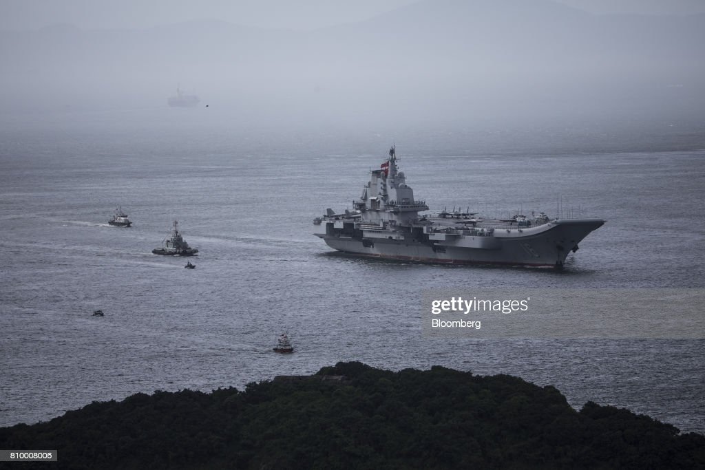 The People's Liberation Army (PLA) Liaoning aircraft carrier, right, sails into Hong Kong, China, on Friday, July 7, 2017. The carrier will visit Hong Kong between July 7 and 11. Photographer: Justin Chin/Bloomberg via Getty Images