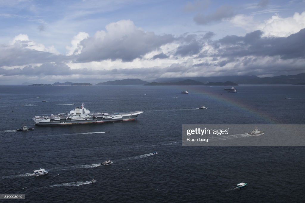 The People's Liberation Army (PLA) Liaoning aircraft carrier sails past a rainbow in Hong Kong, China, on Friday, July 7, 2017. The carrier will visit Hong Kong between July 7 and 11. Photographer: Justin Chin/Bloomberg via Getty Images