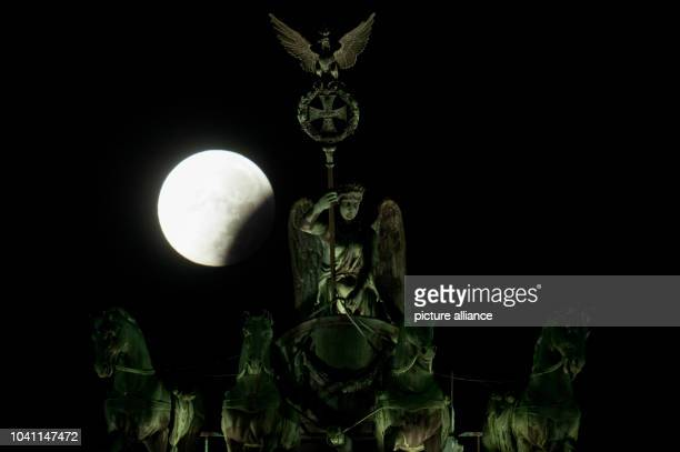 The perigee full moon or supermoon appears red behind the quadriga of the Brandenburg Gate in Berlin Germany 28 September 2015 The combination of a...