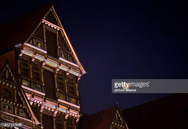 The perigee full moon or supermoon appears red next to the Wedekind house during a total lunar eclipse over Hildesheim Germany 28 September 2015 The...