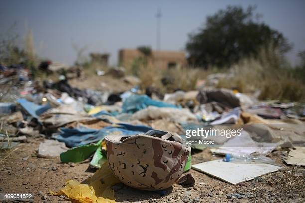 The personal effects of Iraqi troops lie gathered as an Iraqi forensics team unearths bodies from a mass grave in the palace compound of former Iraqi...