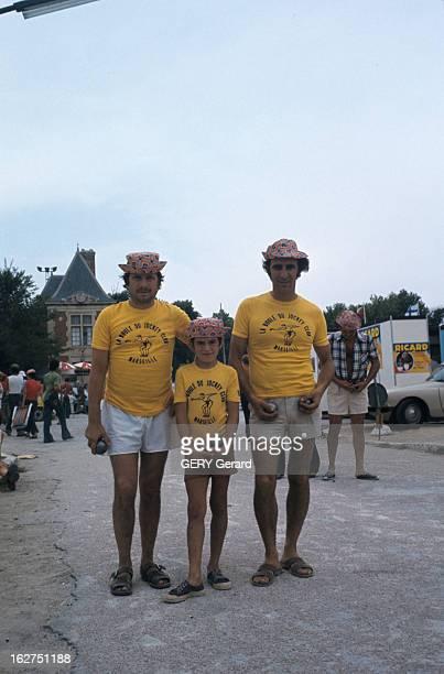 The Petanque Provence juin 1976 La pétanque jeu de boules issu du jeu provençal un enfant entouré de deux hommes tous trois vêtus d'un teeshirt jaune...