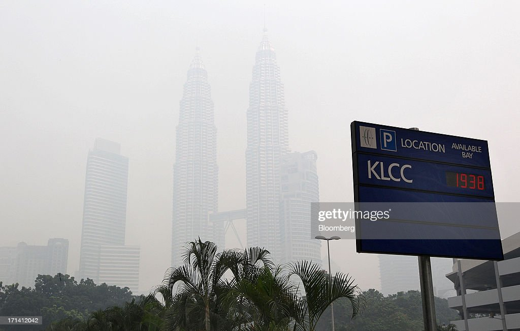 The Petronas Towers, center, stand shrouded in smog in Kuala Lumpur, Malaysia, on Monday, June 24, 2013. Malaysia called for a meeting of Southeast Asian ministers as early as next week after haze from illegal Indonesian forest fires reached hazardous levels in parts of the region. Photographer: Goh Seng Chong/Bloomberg via Getty Images