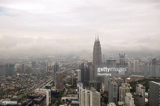 The Petronas Twin Towers stand among other buildings in Kuala Lumpur, Malaysia, on Tuesday, March 18, 2014. Malaysia, aspiring to become a developed...