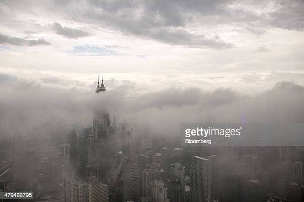 The Petronas Twin Towers stand shrouded by low clouds in Kuala Lumpur, Malaysia, on Tuesday, March 18, 2014. Malaysia, aspiring to become a developed...