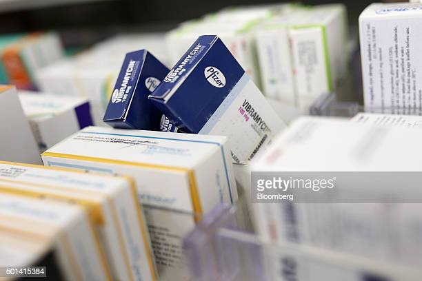 The Pfizer company logo sits on packaging for Vibramycin an antibiotic tablet produced by Pfizer Inc on a pharmacy's shelf in this arranged...