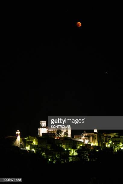 The phase of total eclipse of the moon which turns red on the Castle of Corigliano Calabro in Calabria southern Italy The lunar eclipse is considered...