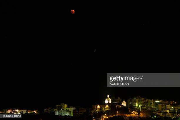 The phase of total eclipse of the moon which turns red on the Church of Sant'Antonio of Corigliano Calabro in Calabria southern Italy The lunar...