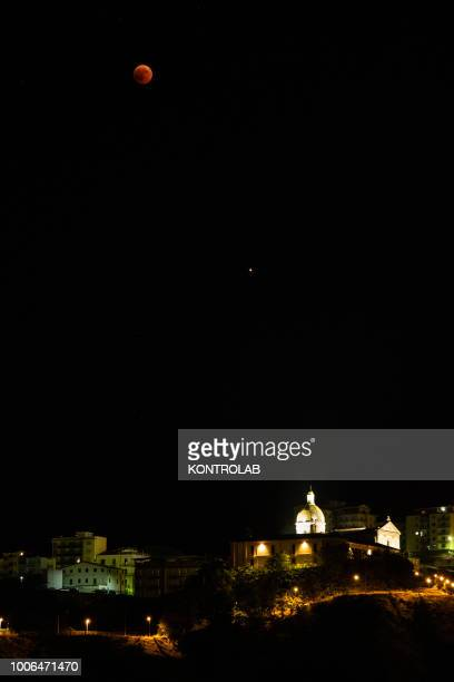 The phase of total eclipse of the moon which turns red over the Church of Sant'Antonio of Corigliano Calabro in Calabria southern Italy The lunar...
