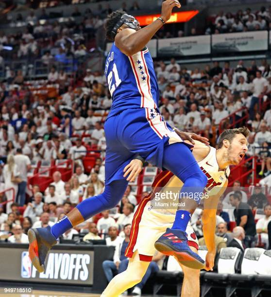 The Philadelphia 76ers' Joel Embiid lands on the Miami Heat's Goran Dragic after Dragic's firstquarter shot in Game 4 of the firstround NBA Playoff...