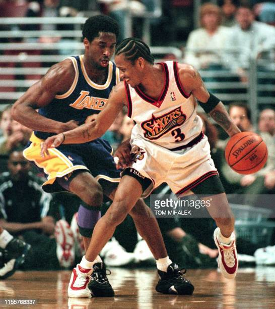 The Philadelphia 76ers point guard Allen Iverson smiles as he moves past the Los Angeles Lakers Kobe Bryant on his way to the basket 19 March 1999 in...