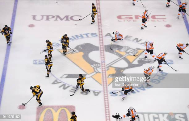 The Philadelphia Flyers and the Pittsburgh Penguins warm up at center ice before Game One of the Eastern Conference First Round in the 2018 NHL...