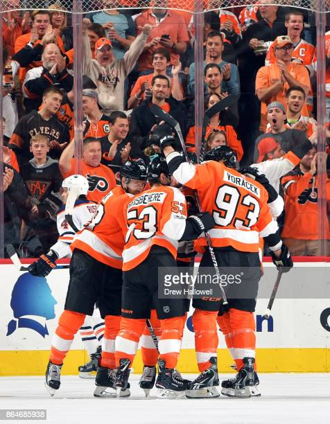 The Philadelphia Flyers congratulate teammate Claude Giroux after scoring a goal in the first period against the Edmonton Oilers at the Wells Fargo...