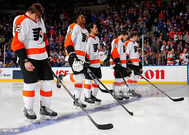 The Philadelphia Flyers line up for the national anthem prior to their game against the New York Islanders at Nassau Veterans Memorial Coliseum on...