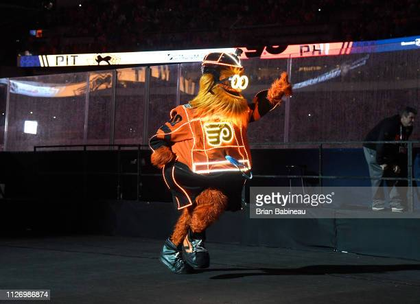 The Philadelphia Flyers mascot Gritty jogs on the field after rappeling down to the ice before the 2019 Coors Light NHL Stadium Series game between...