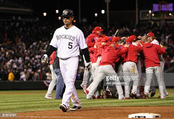 The Philadelphia Phillies celebrate their 54 win as Carlos GOnzalez of the Colorado Rockies walks off the field dejected after Game Four of the NLDS...