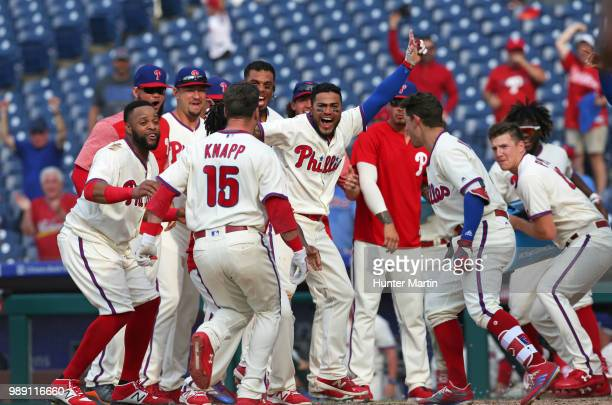 The Philadelphia Phillies surround home plate to celebrate with Andrew Knapp after he hit a game winning walk off solo home run in the 13th inning...