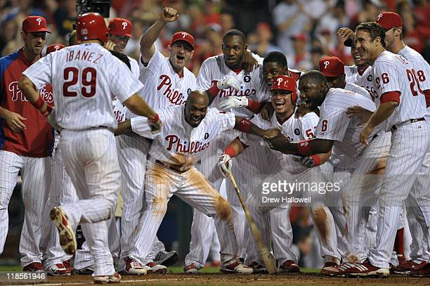 The Philadelphia Phillies wait at home plate for teammate Raul Ibanez after he hit a walkoff home run in the bottom of the 10th inning to beat the...