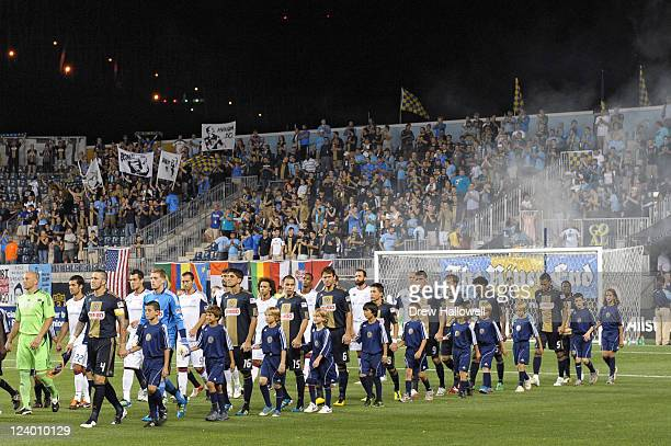 The Philadelphia Union and New England Revolution walk onto the field before the game at PPL Park on September 7 2011 in Chester Pennsylvania The...