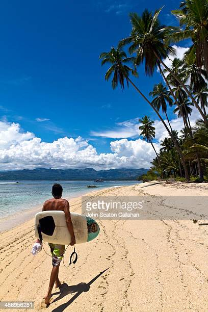 The Philippines, Mindanao, Davao Oriental, surfer walking on empty beach .